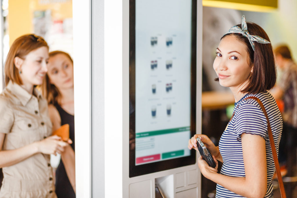 women smiling while ordering food from a self ordering kiosk