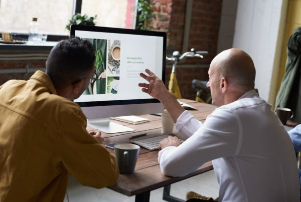 two men using imac computer looking at website design