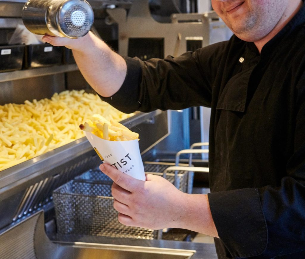 man pouring salt on chips in a cone for takeaway
