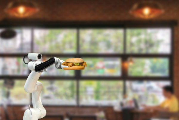 robotic arm serving hamburger in restaurant of the future