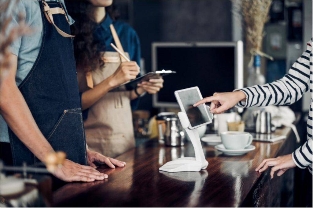 Customer orders on digital kiosk in restaurant
