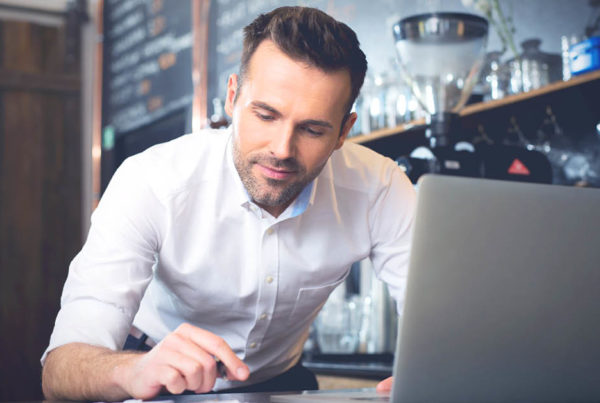 Smiling man learning from restaurant marketing experts on his laptop