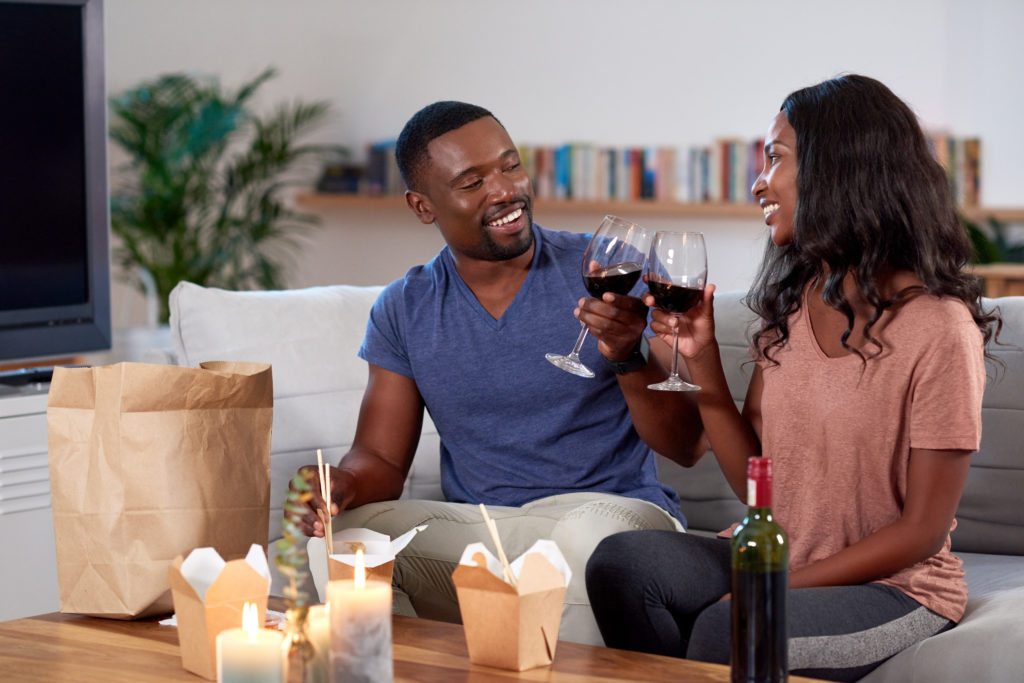 Couple enjoying romantic Valentine's takeaway dinner with glasses of wine