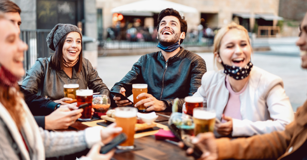 Group of friends gathered around table having beers and laughing